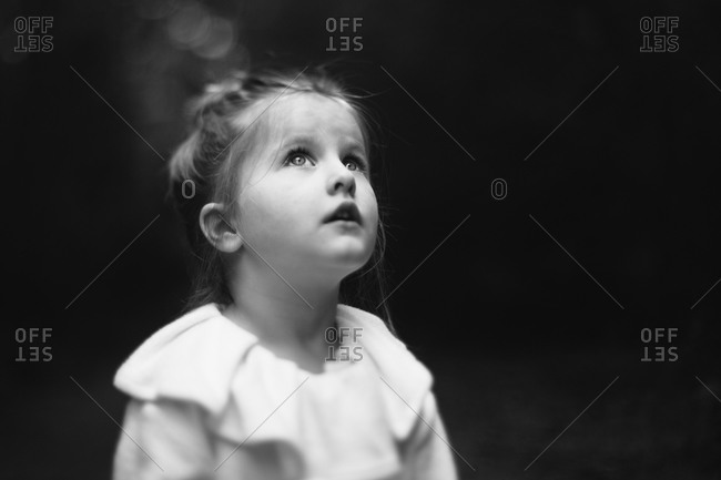 Black and white of little girl in white coat looking up