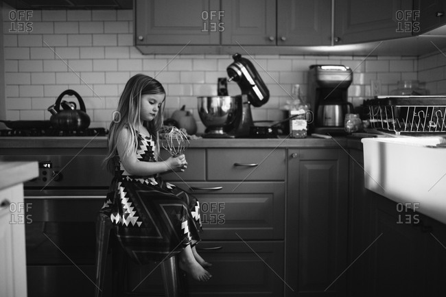 Black and white of little girl ready to bake in the kitchen