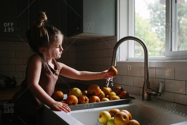 Little girl washing fresh apples in the kitchen sink