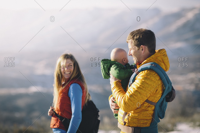 A young couple and their baby hike in the wintry mountains