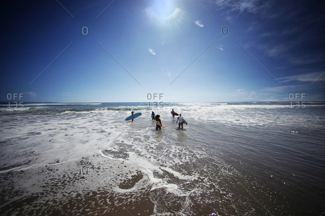 young surfers heading towards the waves for surfing