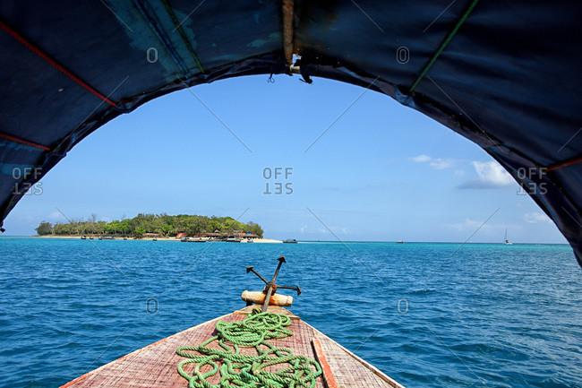 Wooden boat off the beach of Prison Island under blue sky, Zanzibar, Tanzania, Africa