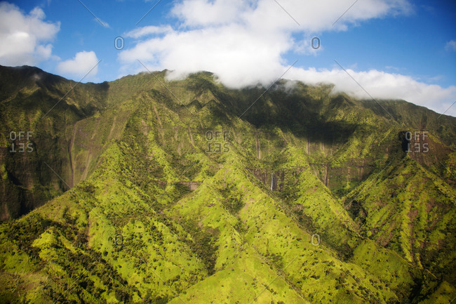Aerial image of lush green mountain slopes under soft clouds and blue sky