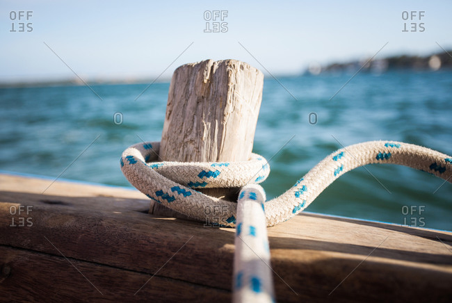 A rope wrapped around an old wood peg on a wooden sailboat adrift in blue water