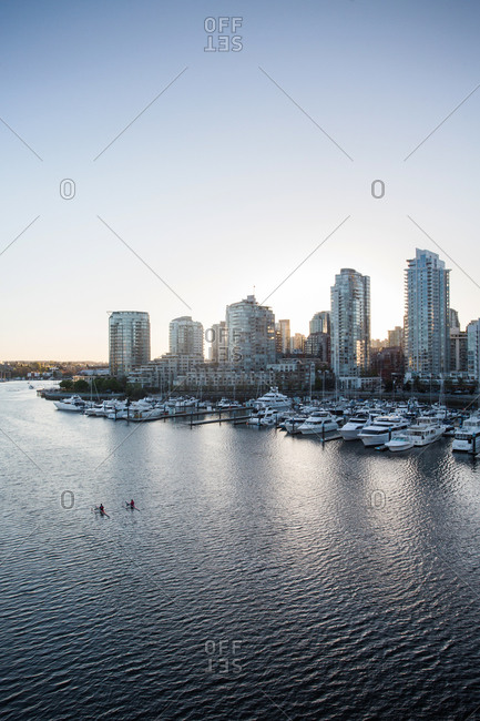 Two rowers passing by an urban marina