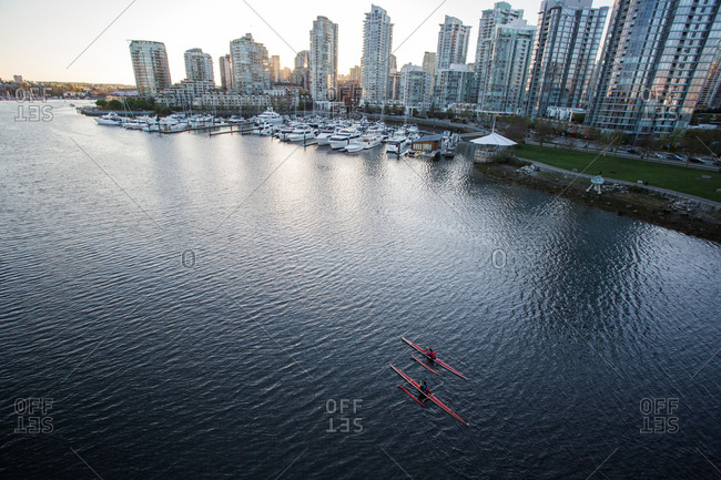 Two rowers paddle through calm water with downtown skyline in distance