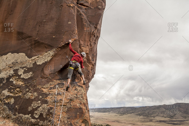 A man rock climbing a desert sandstone tower, Naturita, Colorado
