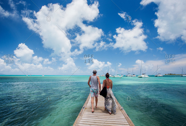 A couple walks down a long dock surrounded by teal sea and blue sky