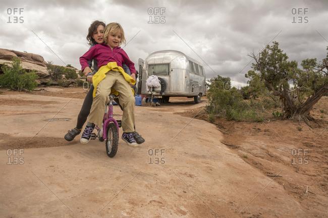 Two girls playing on a tiny mountain bike on desert sandstone, Moab, Utah