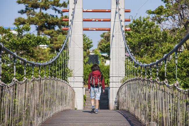 Woman walking over a suspension bridge over river Yongyeon in Jeju Si on Jeju Island