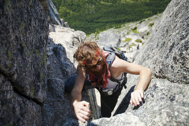 A backpacker climbs up a granite rock chimney en route Needle Peak