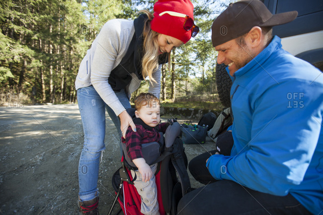 Young parents prepare for a backpacking trip with their child