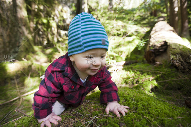 A young boy crawling over a mossy forest floor