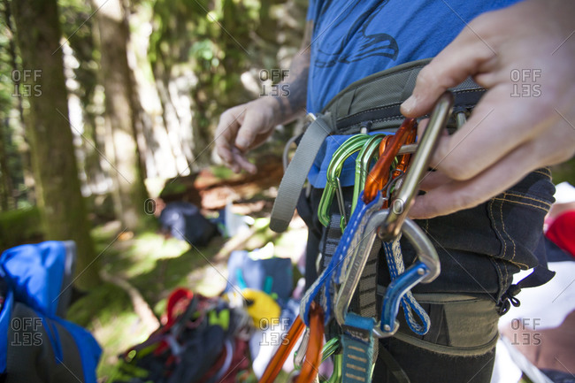 A climber clips a carabineer quick draw on to his harness