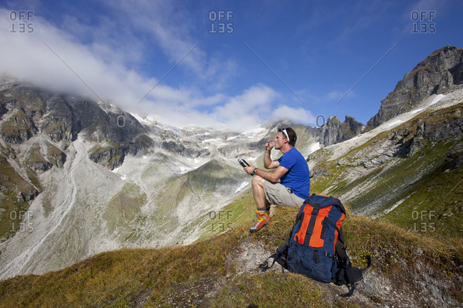 A male hiker drinks a tea during the Glocknerrunde