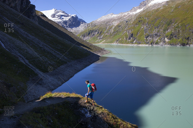A male hiker on the border of shadow and sunlight, high above the Mooserboden lake, during the Glocknerrunde