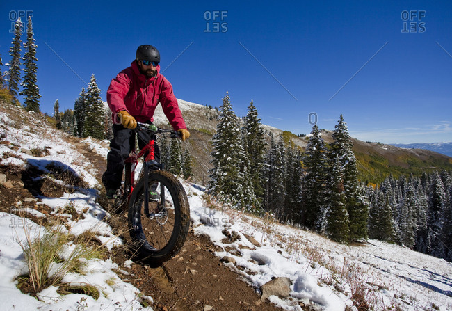 A man wearing red rides a fat tire bike along a trail surrounded by snow during the fall in Utah