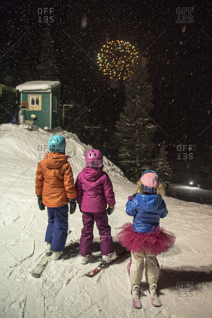 Three girls on skis at night  watching fireworks at  Kendall Mountain's 50th Anniversary Celebration in Silverton, Colorado