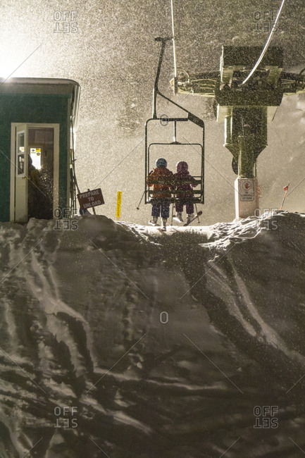 Two girls riding a ski lift on a snowy night skiing at Kendall Mountain's 50th Anniversary in Silverton, Colorado