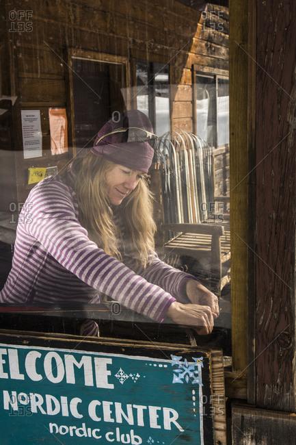 A woman waxing cross country skis on a ski bench at the Nordic Center near Durango, Colorado