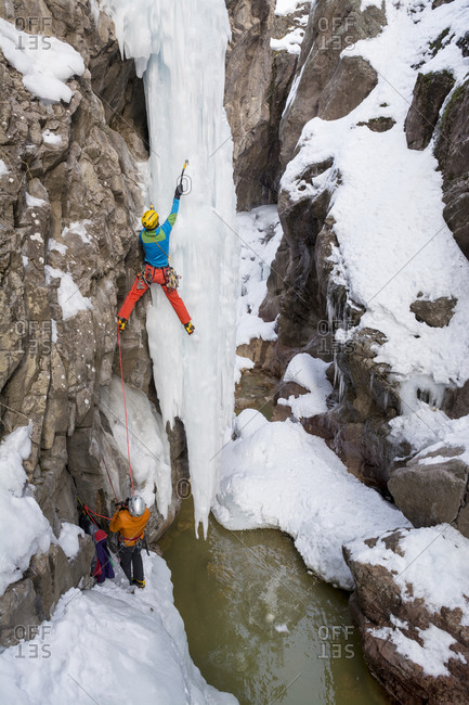 A man and woman ice climbing a frozen waterfall in the Ouray Ice Park, Ouray, Colorado