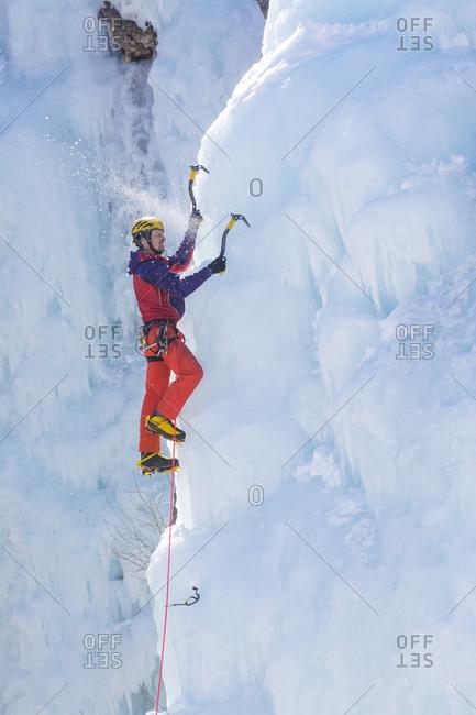 A man ice climbing a frozen waterfall in the Ouray Ice Park, Ouray, Colorado