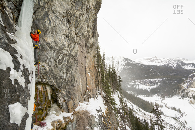 A man and woman ice climbing a frozen waterfall called The Talisman along the Camp Bird Road near Ouray, Colorado