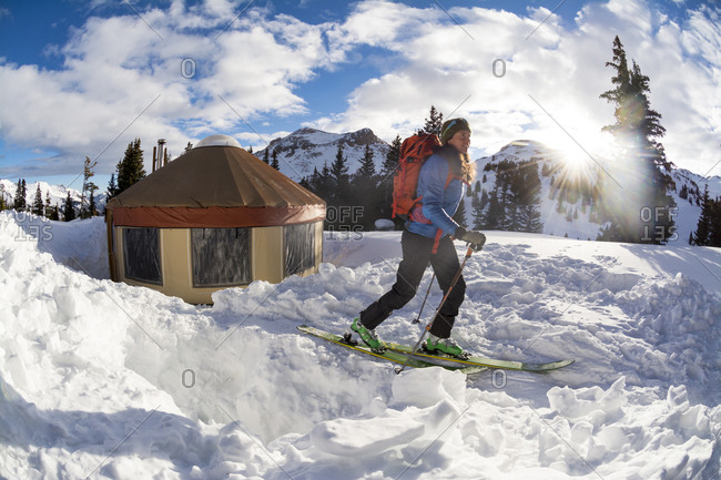 A woman backcountry skiing away from a yurt after camping on Red Mountain Pass, Silverton, Colorado