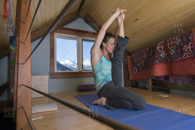 A woman doing yoga in the winter with the La Plata Mountains in the window, Mayday, Colorado