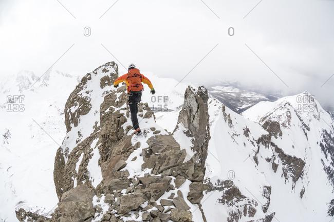 A man climbing Lizard Head Peak in the Lizard Head Wilderness, Uncompahgre National Forest, Telluride, Colorado