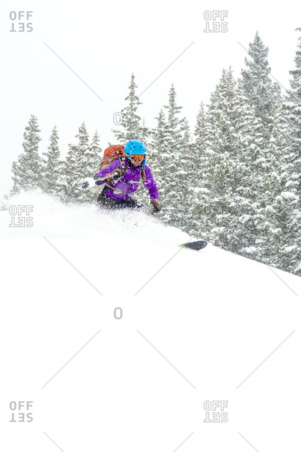 A woman backcountry skiing on a snowy day above Red Mountain Pass in the  Uncompahgre National Forest, Silverton, Colorado