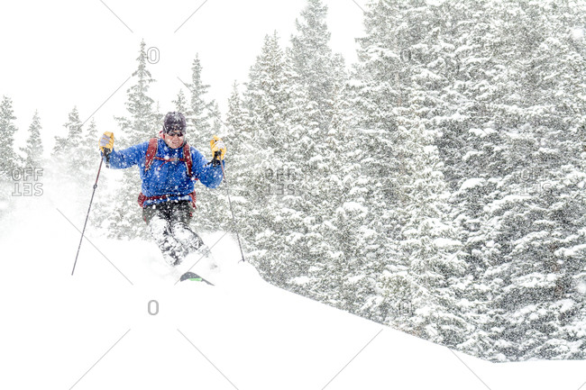 A man backcountry skiing on a snowy day above Red Mountain Pass in the  Uncompahgre National Forest, Silverton, Colorado