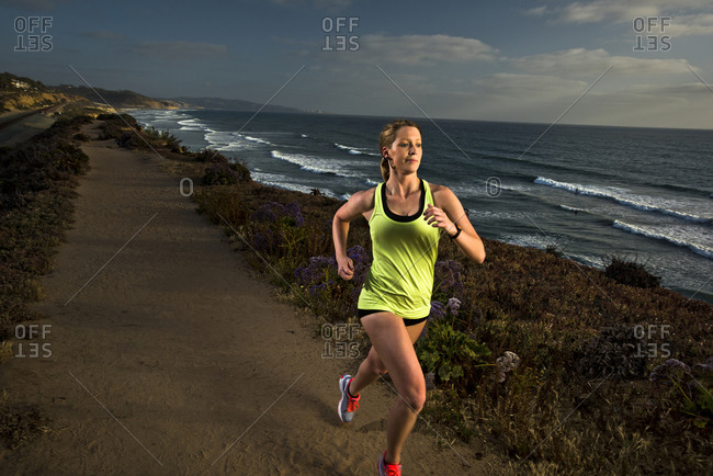 A girl runs on a trail overlooking the beach in San Diego, California