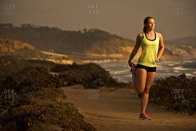 A girl stretches before running on a trail overlooking the beach at sunset in San Diego, California