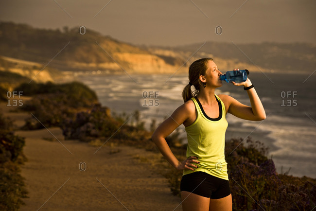 A girl drinks water while taking a break from her run on a trail overlooking the beach at sunset in San Diego, California