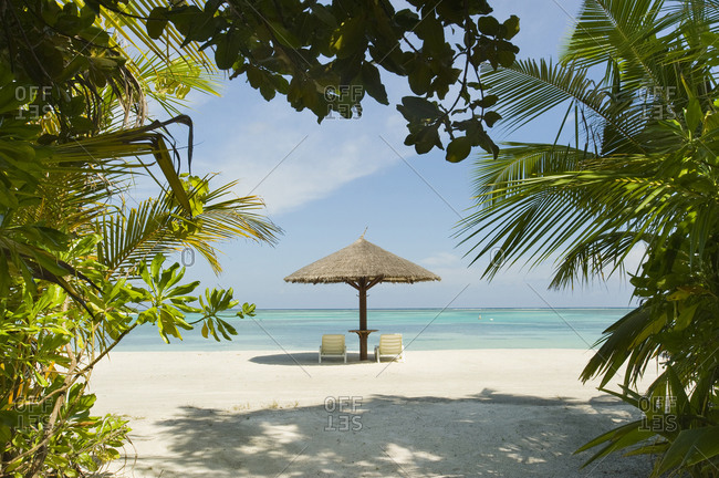 Lounge chairs and a palapa umbrella on the beach at an island resort in South Male Atoll, Maldives