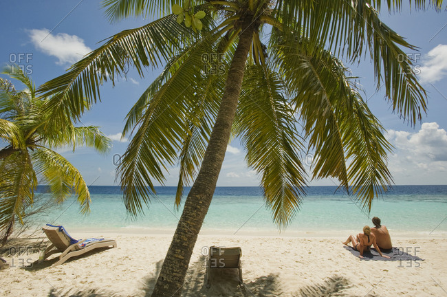 A couple relaxes on the beach at an island resort in South Male Atoll, Maldives