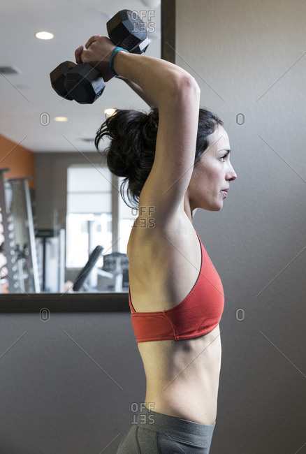 Thin and athletic female weight training in her gym