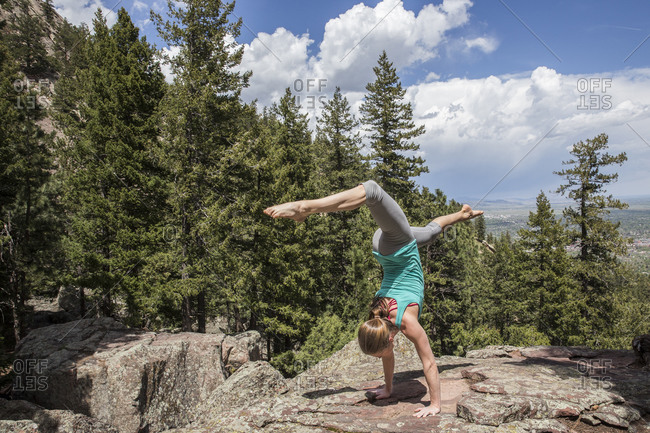 Flexible and strong female holds a hand stand on the rocks in Boulder, Colorado