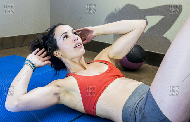 Young, fit Female training her core muscles with bicycle sit-ups