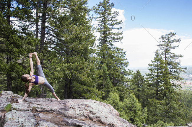 Strong and flexible woman practices yoga on the rocks in Boulder, Colorado
