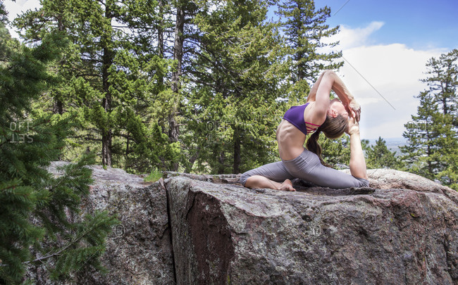 Flexible female practices yoga on the rocks outside in Boulder, Colorado
