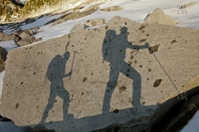 The shadows of two backpackers on a large rock en route Conway Peak, British Columbia, Canada