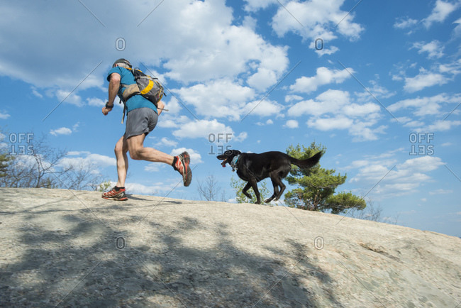 Trail runner and his dog running to the summit of Cathedral ledge in New Hampshire