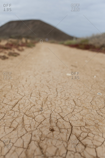 Dry cracked earth in Fuerteventura with a volcanic cone in the background