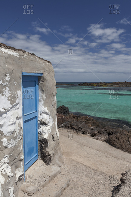 Blue wooden door of an old house in Lobos Island with clear blue ocean in the background