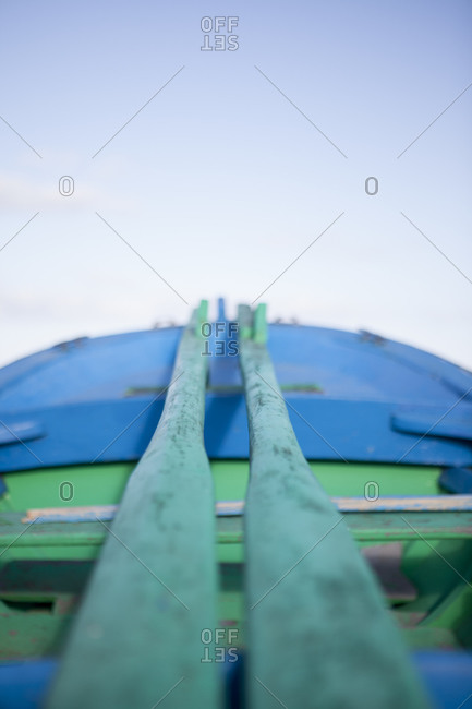 Blue and green wooden boat with wooden oars parked on the beach with no one around