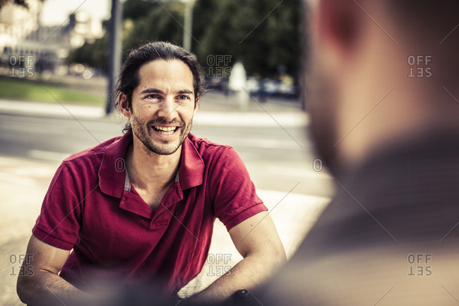 Two men talking to each other at a park in Berlin, Germany