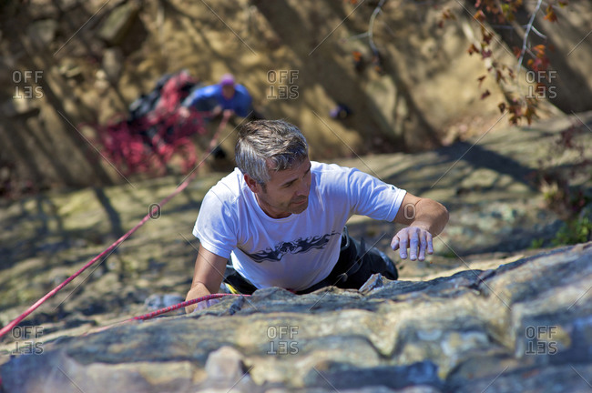 A man rock climber as his partner belays him from the ground on a warm fall day