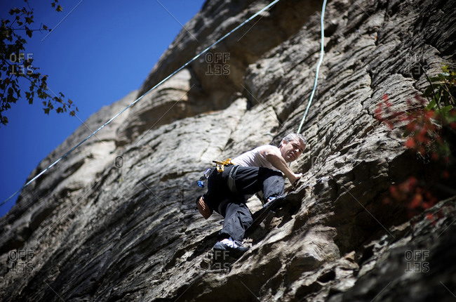 A male rock climber climbs a limestone rock face in the Red River Gorge, KY on a warm fall day